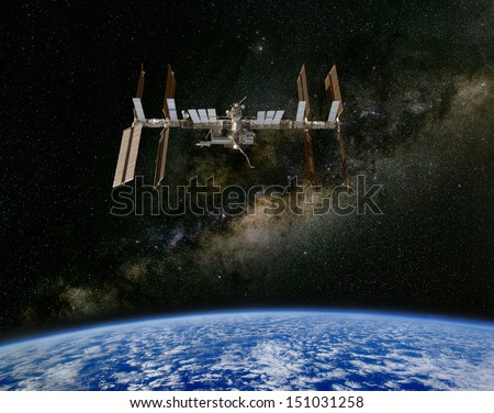 The International Space Station above the Earth, with the Milky Way in the Background. Elements of this image furnished by NASA. - stock photo