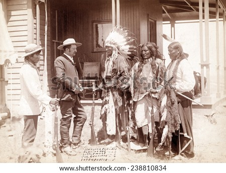 The Interview. Three Cheyenne men, Standing Elk, No. 1; Running Hog, No. 2; Little Wolf, No. 3, with Col. Oelrich, No. 4; Interpreter, No. 5. Dakota Territory. photo by John C. Grabill, 1887 - stock photo