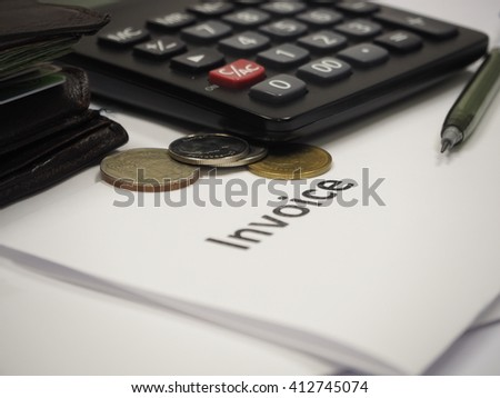 The invoice documents with coins and calculator, selective focus