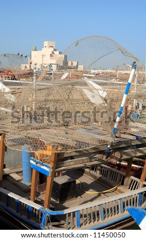 The Islamic Art Museum in Doha, Qatar, seen through traditional fish traps piled on an old dhow in the adjacent harbour. - stock photo