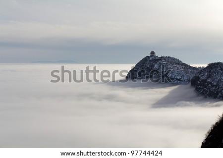 The island on peaceful picturesque cloud sea - stock photo
