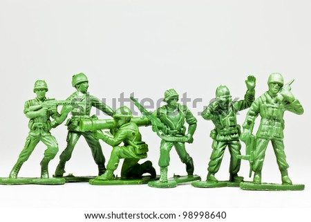 The isolated image of a group of green plastic toy soldiers