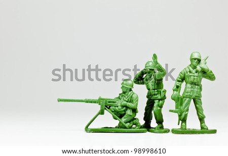 The isolated image of three green plastic toy soldiers - stock photo