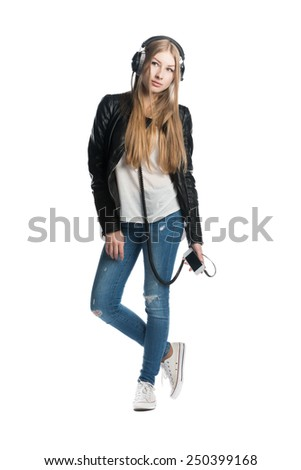The isolated on white portrait of a serious teenager girl in wired headphones listening music from personal phone - stock photo