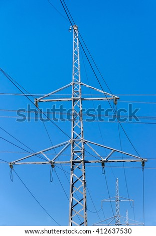 The isolated  transmission towers with wires on the background of the blue sky