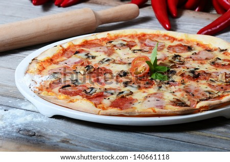The Italian pizza with ham and mushrooms - stock photo