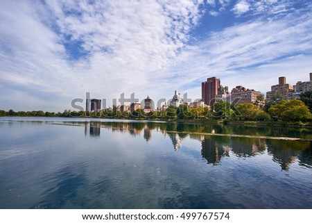 The Jacqueline Kennedy Onassis Reservoir in Central Park with the surrounding apartment buildings mirroring in the calm surface