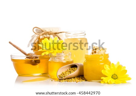 The jars of honey, one of them with honeycombs, glass bowl with honey and wooden scoop with pollen isolated on white - stock photo