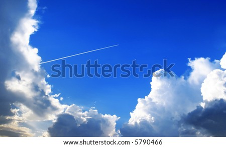 The jet plane in a stratosphere, reserves an equal white loop, the bright blue sky, the low cumulus clouds illuminated by the evening sun.