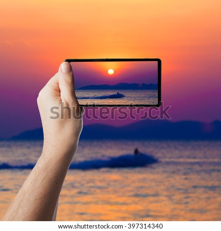 the jetski above the water at sunset.  Taking photo on smartphone - stock photo
