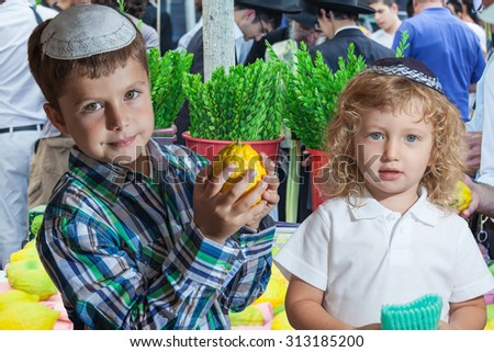 The Jewish holiday of Sukkot. Cute little boy with long blond hair in  knitted skullcap and  seven year old boy in white skullcap with etrog. They stand  on a pre-holiday market in Jerusalem.    - stock photo