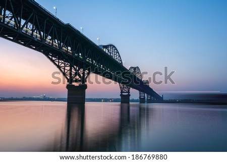 the jiujiang yangtze river bridge in nightfall ,for double railway, highway bridge.  - stock photo