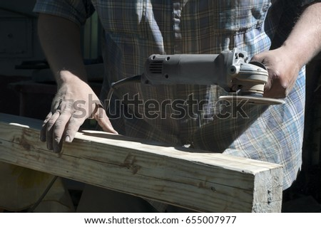 The joiner works the grinder in the sunlight.