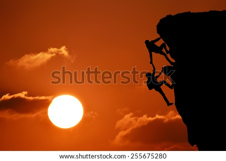 The joint work teamwork of two men travelers help each other on top of a mountain climbing team, a beautiful sunset landscape with big sun,sunset - stock photo