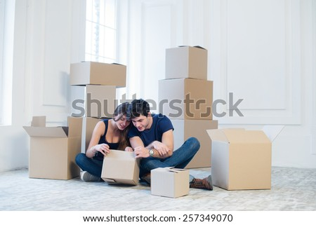 The joy of moving into the house. A loving couple holding box in hands and looking in the box while a young and beautiful couple in love sitting on the couch in an empty apartment among boxes - stock photo