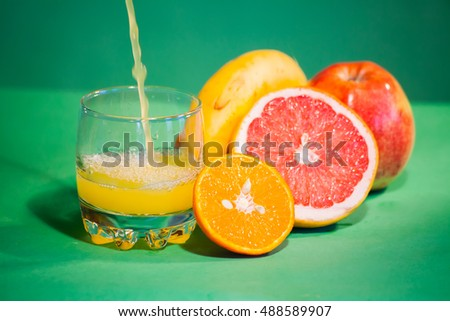 the juice is poured into a glass. Against the background of grapefruit, mandarin, banana and apple