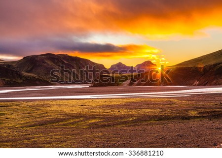 The July morning in the National Park Landmannalaugar, Iceland. Mountains and glaciers covered with warm pink and orange sun - stock photo