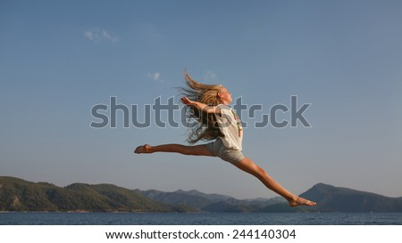 The jump, flight above the sea  and mountains of the young girl about 9-12 years old with the blonde and loose hair in the rays of the setting sun. She wears top-shirt and shorts.