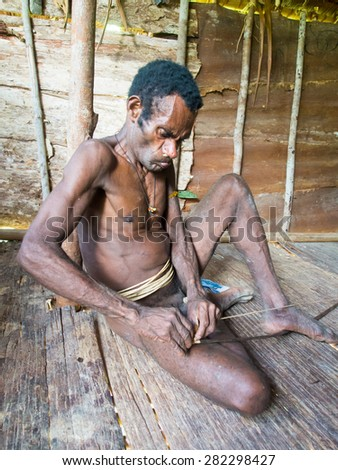 The jungle, Indonesia - January 15, 2015: A man from the Korowaya tribe met when hiking through the jungle