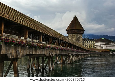 The Kapellbrucke (Chapel Bridge) is a covered wooden footbridge spanning diagonally across the Reuss River in the city of Lucerne, Switzerland