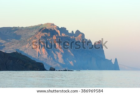The Kara-Dag mountain is an inactive volcano. The rocky mountains over sea surface in the evening haze. This area is a nature reserve in Crimea. - stock photo