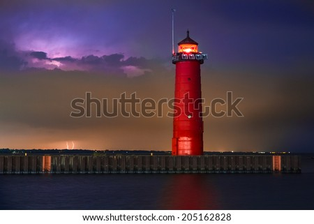 The Kenosha North Pier Lighthouse, on Wisconsin's Lake Michigan coast, shines brightly with lightning illuminating a cloudy night sky. - stock photo
