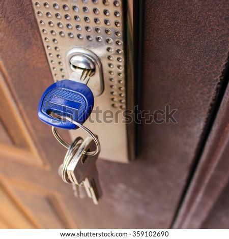 The key in the lock of the iron door.  - stock photo