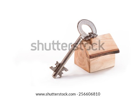 The key to the lock on the door and a model house on a white background - stock photo