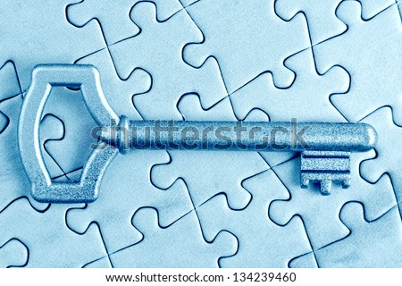 The key to the puzzle close in cold tones. - stock photo
