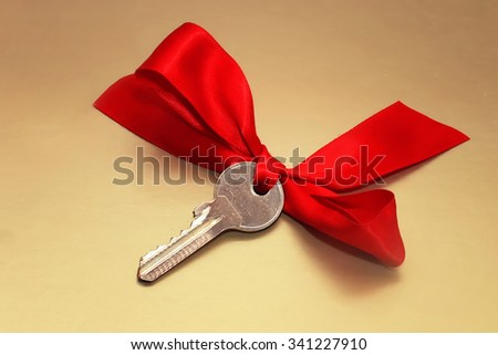 the key with a red bow on a gold background - stock photo