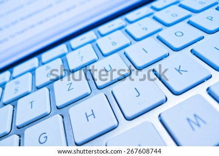 the keyboard of a computer in front of a screen. computer and internet - stock photo