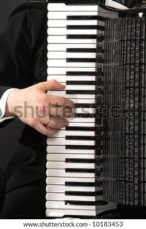 The keyboard of an accordion with a hand of the musician - stock photo
