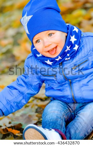 The kid in a blue cap and a jacket sitting in yellow leaves in autumn park. Cheerful baby sitting in the park in the leaves.