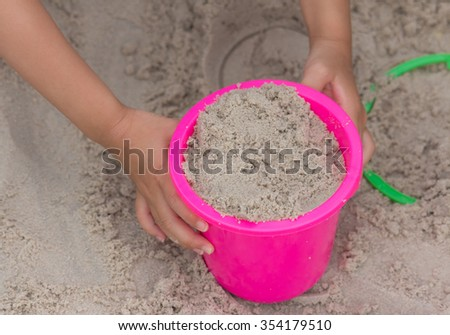 The kid playing plastic bucket toys with sand on the beach - stock photo