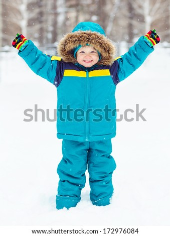 The kid put his hands up, photo winter outdoors. - stock photo