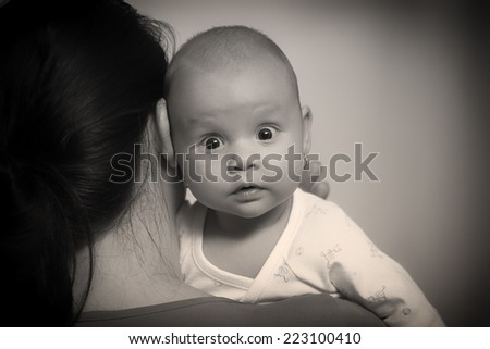 The kid sits on his mother's arms and looks out over her shoulder. Black and White photography