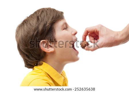 The kid tries to bite chocolate ball in man hand, isolated on white background - stock photo
