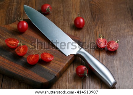 The kitchen knife and cut the tomatoes on the board