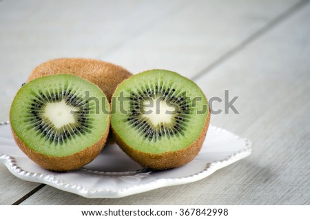 The kiwi fruits on the table on a white vintage plate