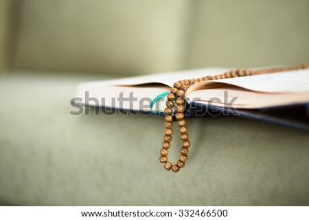 The Koran with rosary beads - stock photo
