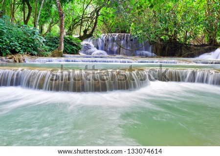 The Kuang Si Falls, sometimes spelled Kuang Xi, is a three tier waterfall about 29 kilometers (18 mi) south of Luang Prabang in Laos. - stock photo
