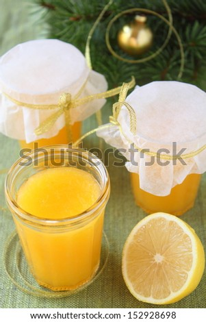 the Kurd from lemons in glass jars on a table with cristmas tree branches