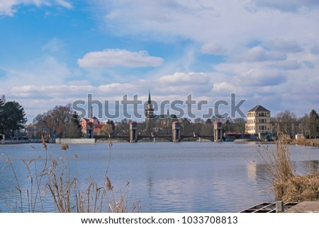 The Labe River and Hydroelectric plant in Nymburk, Czech republic. church of St. Giles on background