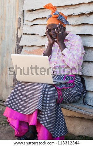 The lady is shocked by what the computer reveals. - stock photo