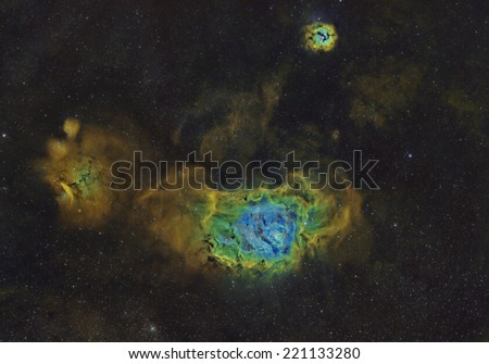 The Lagoon and Trifid Nebulae Imaged in Narrow Band and Mapped to the Hubble Space Palette - stock photo