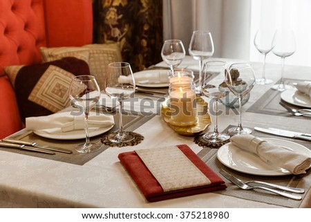 The laid table at restaurant and a sofa in pillows - stock photo