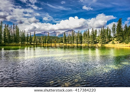 The lake is surrounded by evergreen firs. Small lake in the Rocky Mountains of Canada