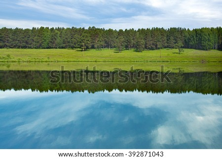 The lake landscape, meadow, forest and sky