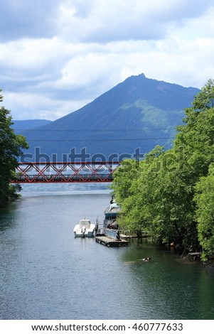 the lake shikotsu. A mountain and river with a red iron bridge