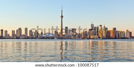 The landmark Toronto downtown view from the center island. Scenic view of the Tower illuminated by the iconic downtown skyline of skyscrapers and high rise condominiums reflecting in Lake Ontario